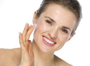 Beauty portrait of smiling young woman applying creme